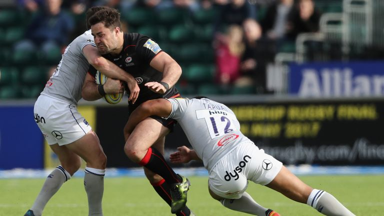 Brad Barritt of Saracens is tackled by Bath's George Ford (L) and Ben Tapuai
