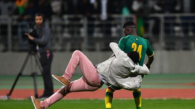 A pitch invader tackles Senegal's Lamine Gassama