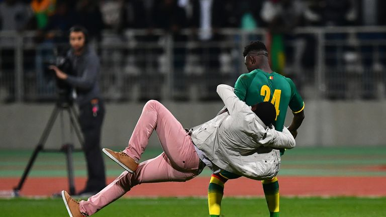PARIS, FRANCE - MARCH 27:  A pitch invader tackles Lamine Gassama of Senegal during the International Friendly match between the Ivory Coast and Senegal at