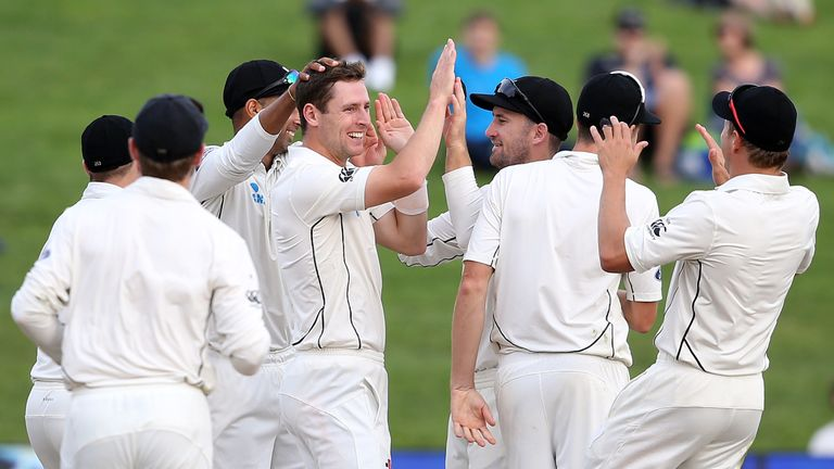 Matt Henry (C) of New Zealand celebrates with teammates after taking the wicket of Temba Bavuma of South Africa during day four of the third Test cricket m