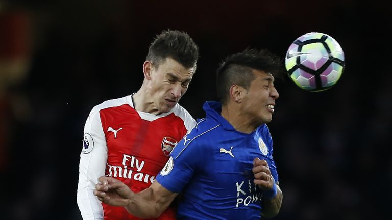 Leonardo Ulloa vies with Laurent Koscielny