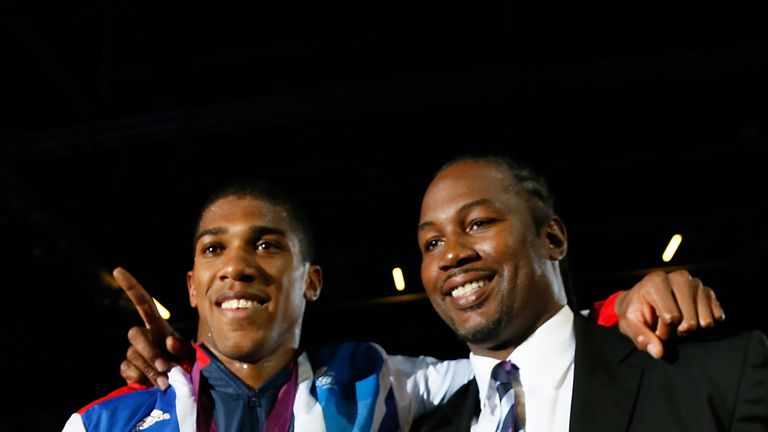 Gold medalist Anthony Joshua (L) celebrates with former world heavweight boxing champion and fellow countryman Lennox Lewis (R) during the awards ceremony