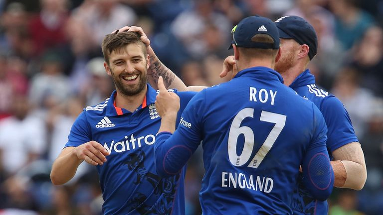 England bowler Mark Wood (L) celebrates with England's Ben Stokes and England's Jason Roy (2nd L) after taking the wicket of Pakistan's Babar Azam (not pic