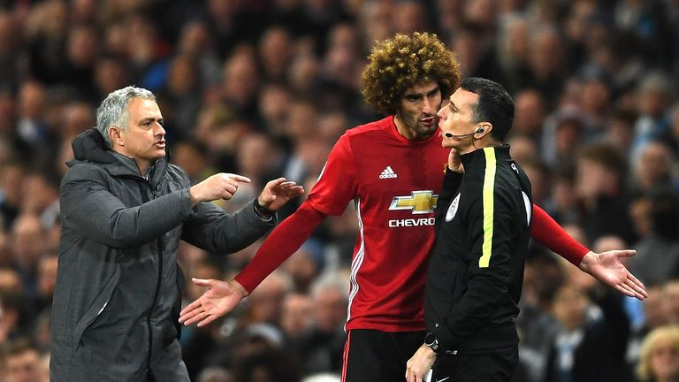 Marouane Fellaini protests his dismissal to the fourth official