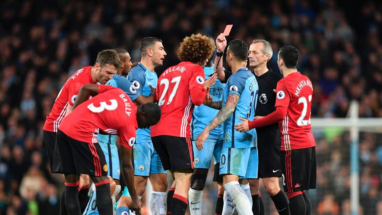 Referee Martin Atkinson sends off Manchester United's midfielder Marouane Fellaini