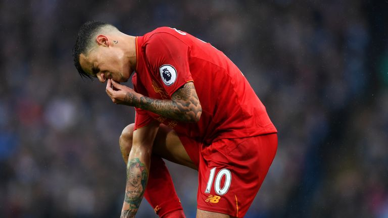 Philippe Coutinho of Liverpool goes down injured and holds his mouth during the Premier League match between Manchester Ci