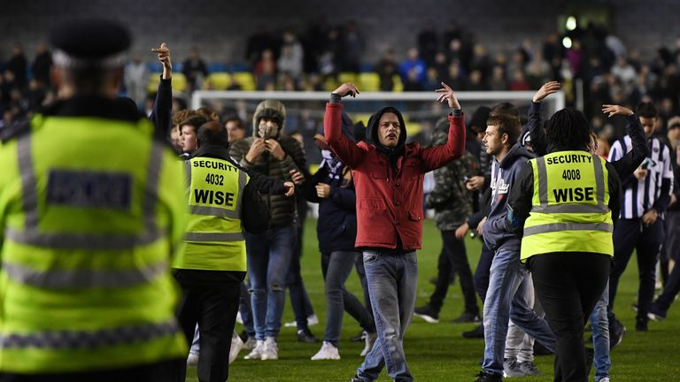 Fans invade the pitch after Millwall's 0-0 draw with Scunthorpe