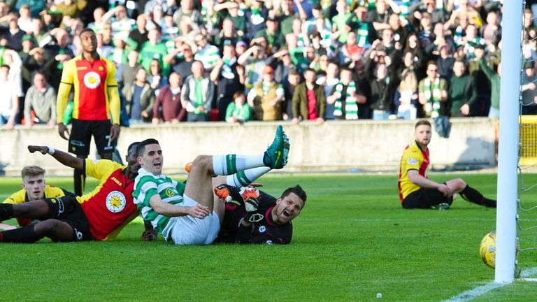 Rogic (seated) watches the ball slide over the line