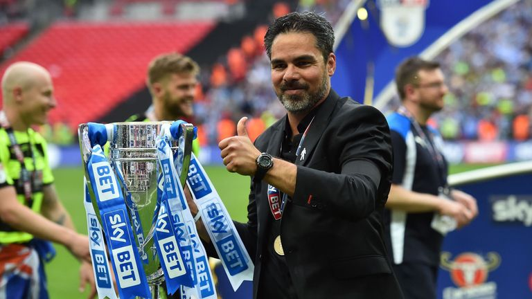 Huddersfield Town's German head coach David Wagner gestures as he holds the Championship Playoff trophy on the pitch after winning the penalty shoot-out in
