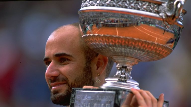 Andre Agassi of the United States celebrates victory with the trophy during the 1999 French Open Final match against Andrei Medvedev