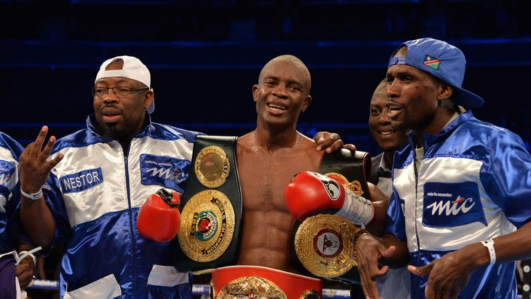 Indongo celebrates with WBA and IBF belts after beating Burns