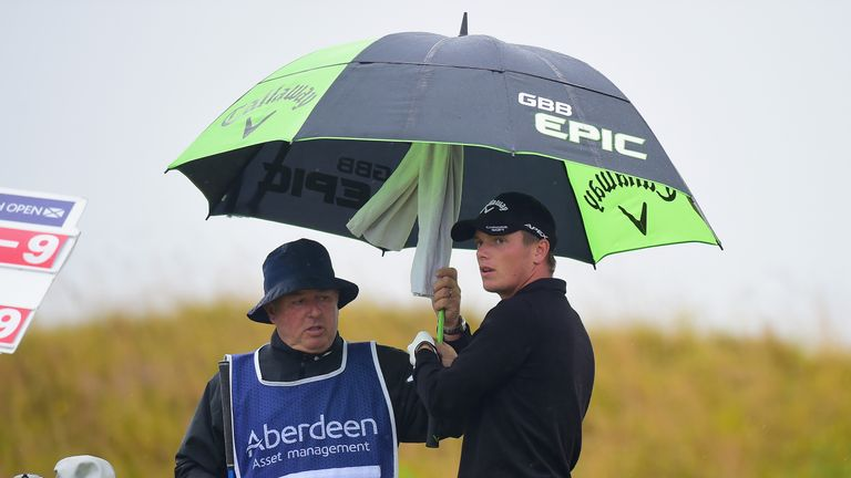 Callum Shinkwin shelters from the rain during the third round of the Scottish Open