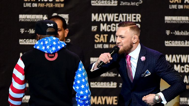 Conor McGregor speaks as Floyd Mayweather walks past as the World Press tour hit Los Angeles