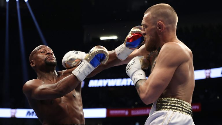 Conor McGregor throws a punch at Floyd Mayweather Jr