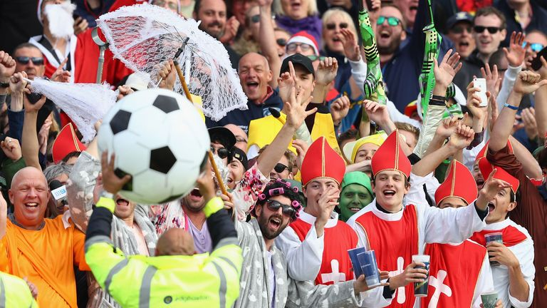 A steward toys with fans before returning their inflatable football