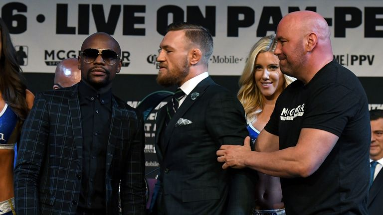 Floyd Mayweather poses as Conor McGregor is pulled back by UFC President Dana White