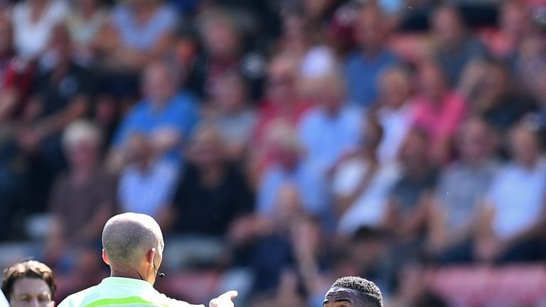 Manchester City midfielder Raheem Sterling (R) gestures to referee Mike Dean after he receives a second yellow card for going into the crowd at Bournemouth
