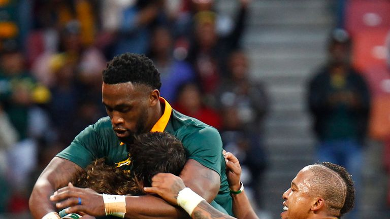 Springboks winger Courtnall Skosan (L/11#) is mobbed by teammates as he celebrates scoring a try during the International Rugby Test match between Argentin