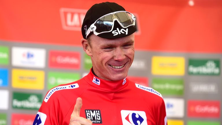 "Sky's British cyclist Christopher Froome smiles as he sports the overall leader's red jersey on the podium of the 20th stage of the 72nd edition of ""La Vue"