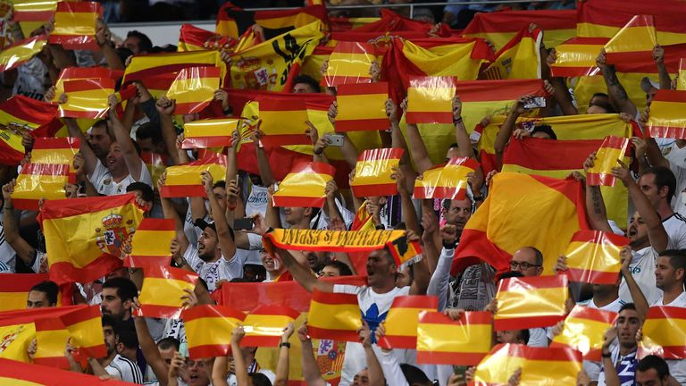 Real Madrid's fans cheer with Spanish flags before their game with Espanyol