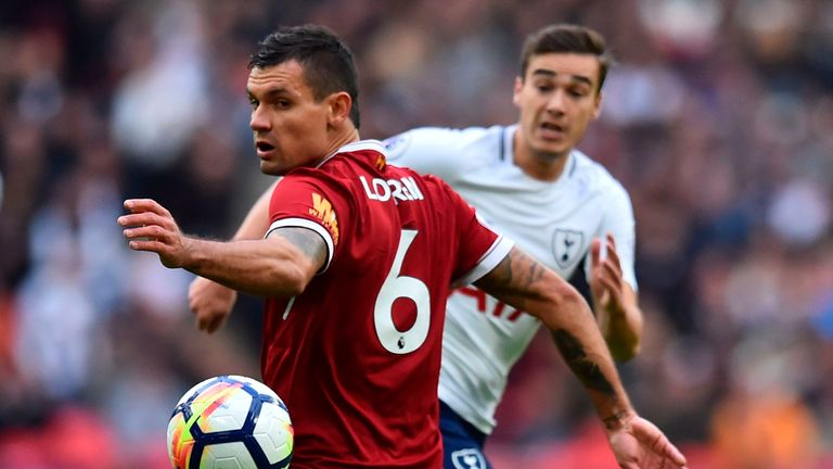 Tottenham Hotspur's English midfielder Harry Winks (R) passes past Liverpool's Croatian defender Dejan Lovren during the English Premier League football ma