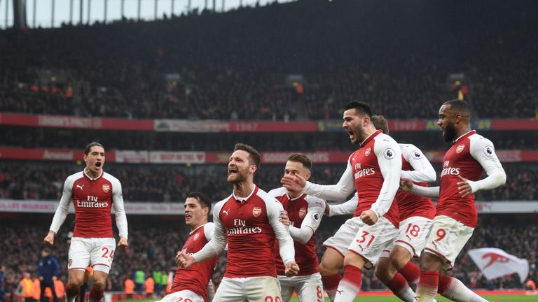 Arsenal players celebrate with Skhodran Mustafi after his opening goal in the win over Tottenham