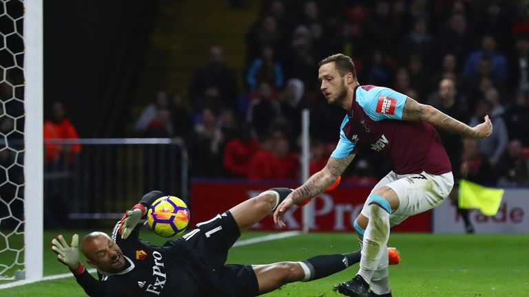 Heurelho Gomes of Watford makes a save from Marko Arnautovic of West Ham United (R)