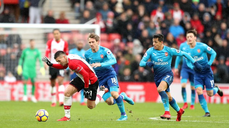 Alexis Sanchez and Nacho Monreal vie for the ball with Dusan Tadic