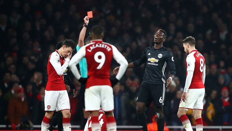 Paul Pogba of Manchester United is shown a red card by referee Andre Marriner (obscured)