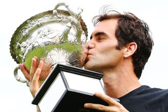 Roger Federer kisses the Norman Brookes Challenge Cup the day after defending his Australian Open title