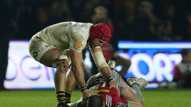 Wasps' James Haskell checks on Harlequins' Jamie Roberts after a late tackle for which he is sent off during the Champions Cup pool one match at Twickenham