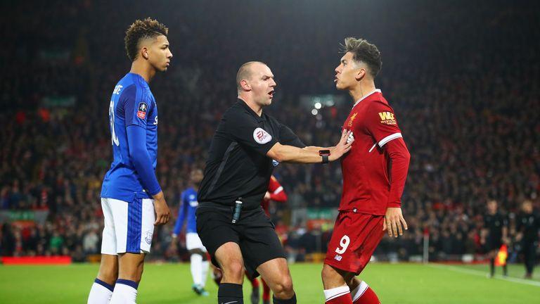 Referee Robert Madley intervenes as Mason Holgate of Everton and Roberto Firmino of Liverpool clash