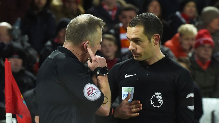 Jonathan Moss consults with his assistant before awarding Tottenham's first penalty at Anfield