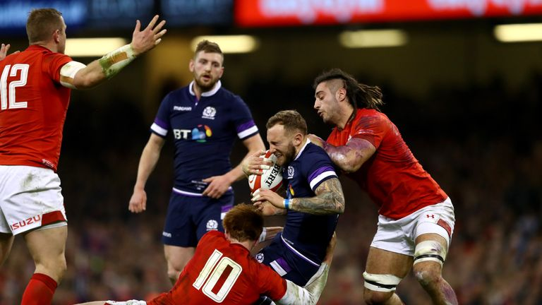 Byron McGuigan of Scotland is tackled by Josh Navidi and Rhys Patchell of Wales