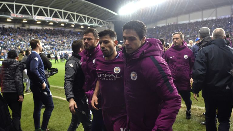 Sergio Aguero of Man City leaves the pitch with assistant coach Mikel Arteta