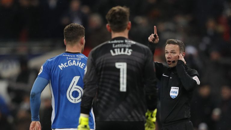 Referee Paul Tierney listens to a VAR decision during the FA Cup replay between Tottenham and Rochdale