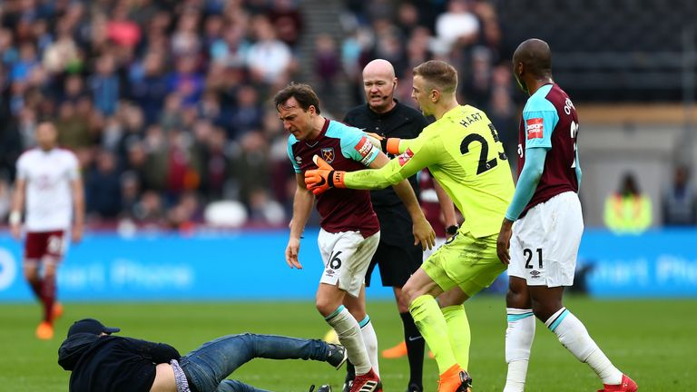 A supporter tussles with West Ham captain Mark Noble during Saturday's match