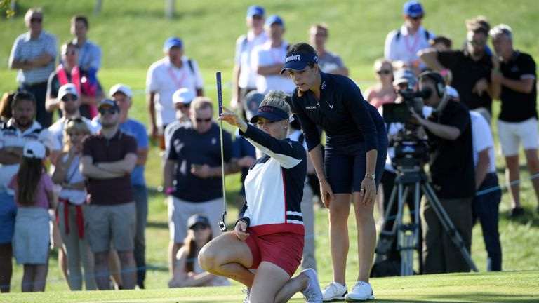 Charley Hull lines up a putt on the fifth green at the GolfSixes as Georgia Hall looks on