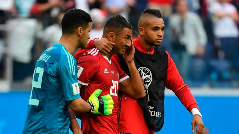Aziz Bouhaddouz (C) is consoled by teammates after his own goal handed Iran all three points in Group B