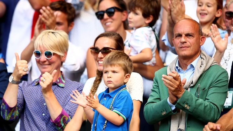 Jelena Djokovic (centre) and their son Stefan applaud Novak's winning display
