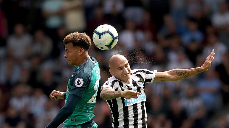 Dele Alli and Jonjo Shelvey compete in the air at St James' Park