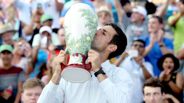 Djokovic celebrates with the trophy after beating Roger Federer in straight sets in the final