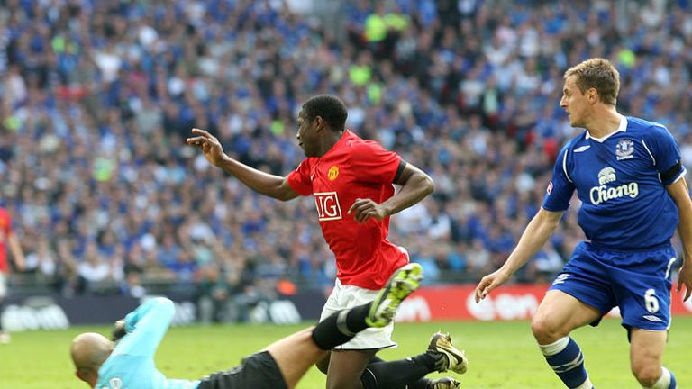 Danny Welbeck falls in the area under a challenge from Tim Howard.