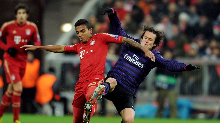 Tomas Rosicky challenges Luiz Gustavo of Bayern Munich during the Champions League Round of 16 second leg match.