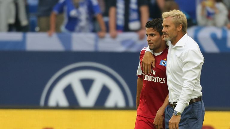 Coach Thorsten Fink of Hamburg hugs Tomas Rincon when they leave the pitch after the Bundesliga match against Schalke.