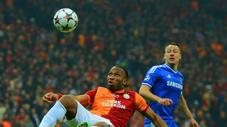 John Terry of Chelsea looks on as Didier Drogba of Galatasaray clears