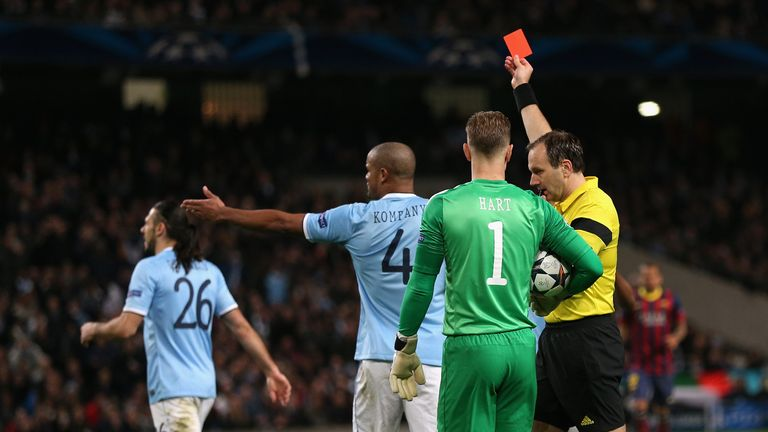 MANCHESTER, ENGLAND - FEBRUARY 18:  Referee Jonas Eriksson shows a red card to Martin Demichelis of Manchester City during the UEFA Champions League Round