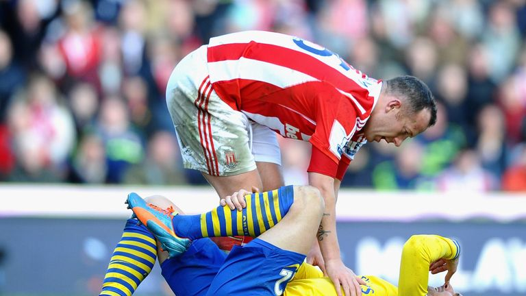 Olivier Giroud of Arsenal is consoled by Charlie Adam of Stoke City