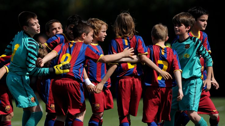 Barcelona youth players do a team cheer prior to playing a match on one of the pitches at the Joan Camper training ground