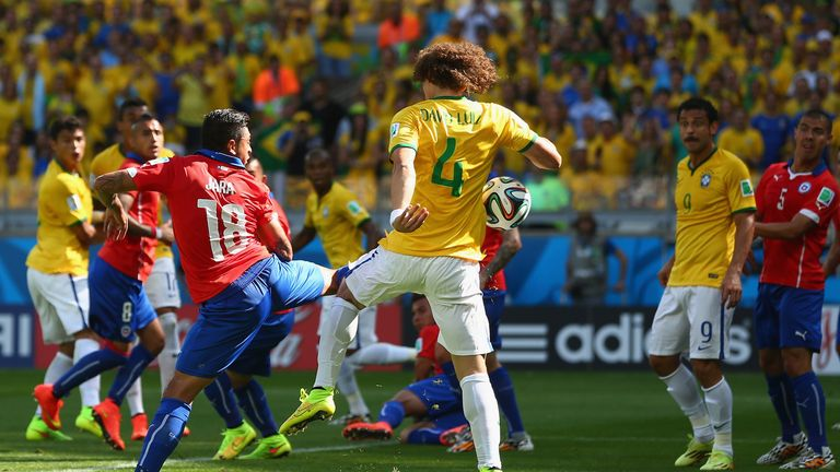 BELO HORIZONTE, BRAZIL - JUNE 28: David Luiz of Brazil scores his team's first goal against Gonzalo Jara of Chile looks on during the 2014 FIFA World Cup